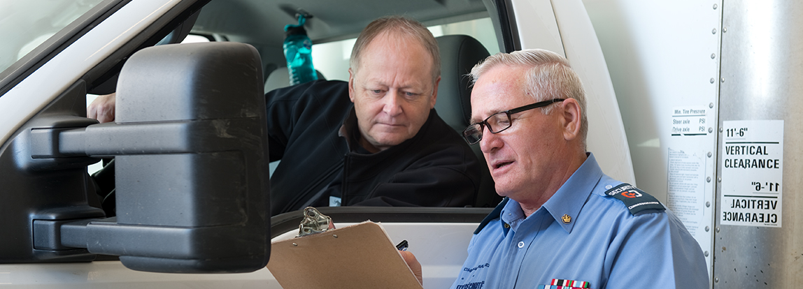An officer going over documents with a truck driver