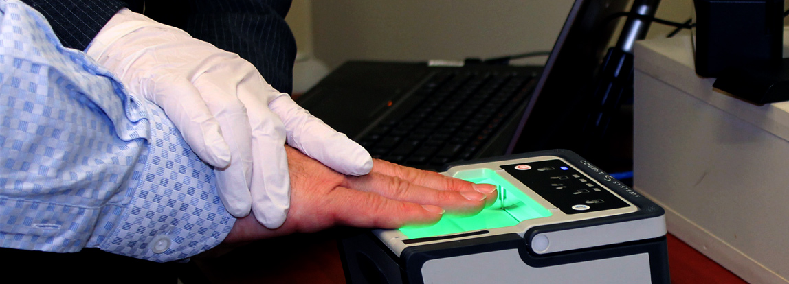 An officer gathering fingerprints from another individual