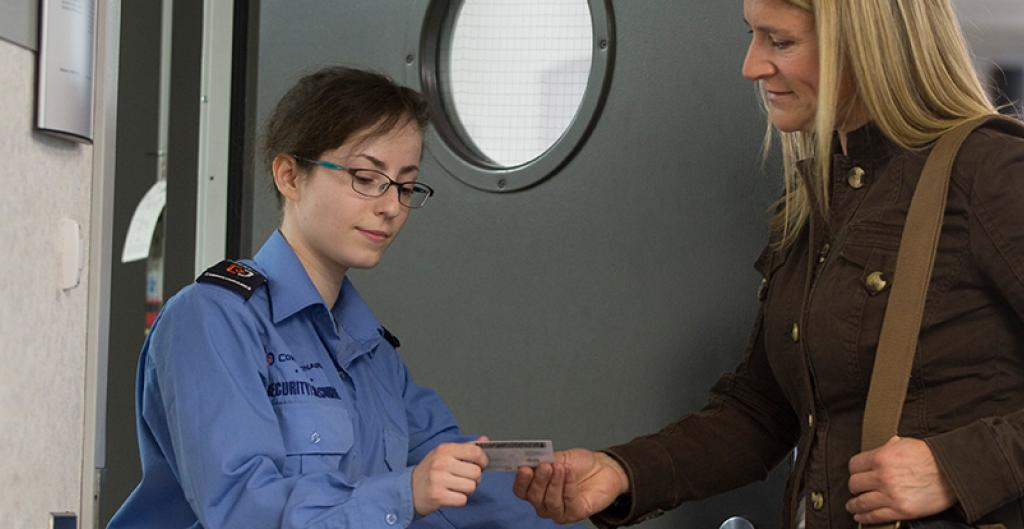 An officer presenting an ID card to an individual